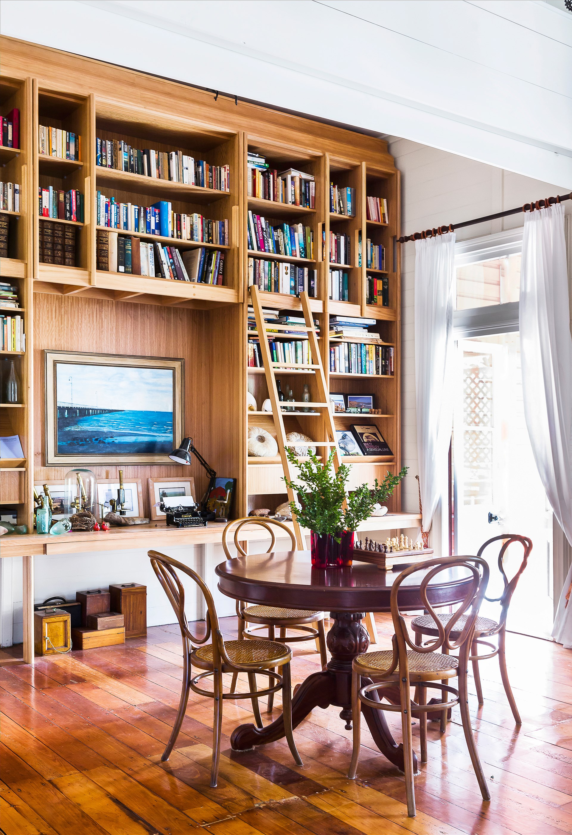 The library-style shelves, designed by Stuart Vokes and made by Desks Etc, contain all manner of books and antiques the family has collected over the years. The vintage table and Bentwood chairs are all eBay finds. Painting by Greg Dwyer. Photo: Maree Homer / *Australian House & Garden*