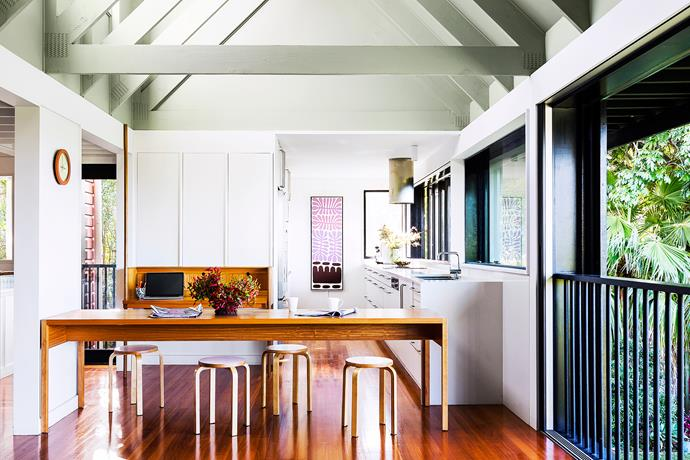 """Large windows open the kitchen to the breezes and a lush garden enhances the verandah effect. **Table** by [Vokes and Peters](http://vokesandpeters.com/?utm_campaign=supplier/