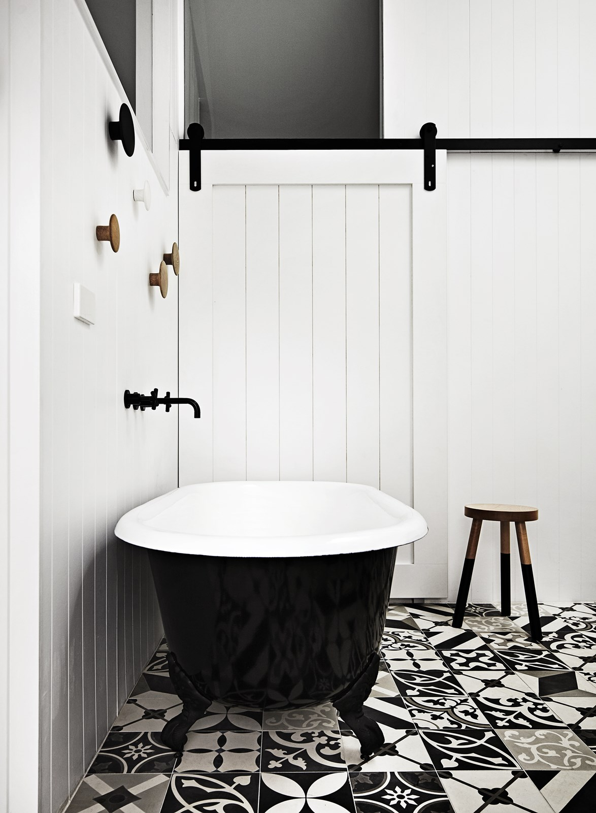 "A crisp black-and-white palette give this bathroom - with a [sliding barn door](https://www.homestolove.com.au/maximise-space-and-style-with-barn-doors-6582|target=""_blank"") -  a modern farmhouse feel. *Photo: Sharyn Cairns / Story: Real Living*"