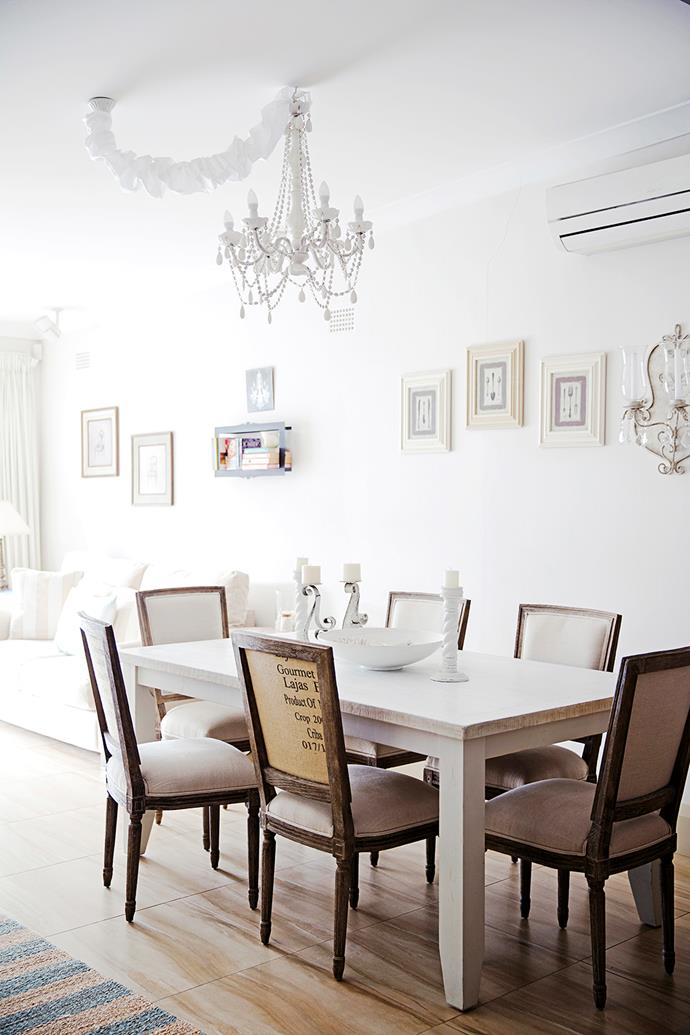 The dining area takes on a French Provincial feel with a striking chandelier and Parisian-style chairs.