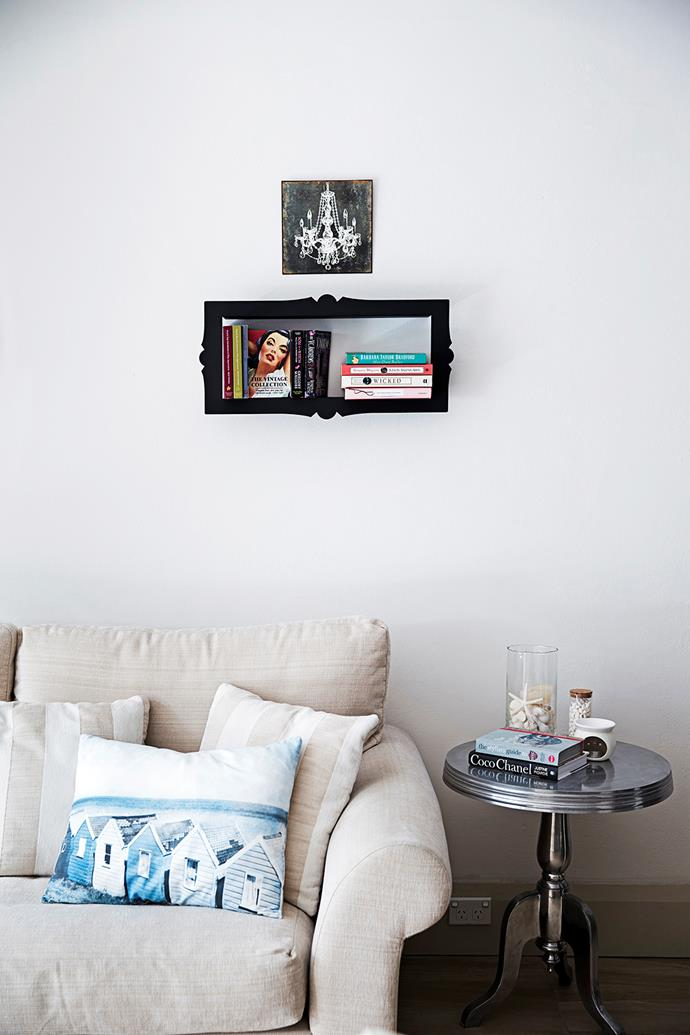 The picture frame shelf displays books and trinkets.