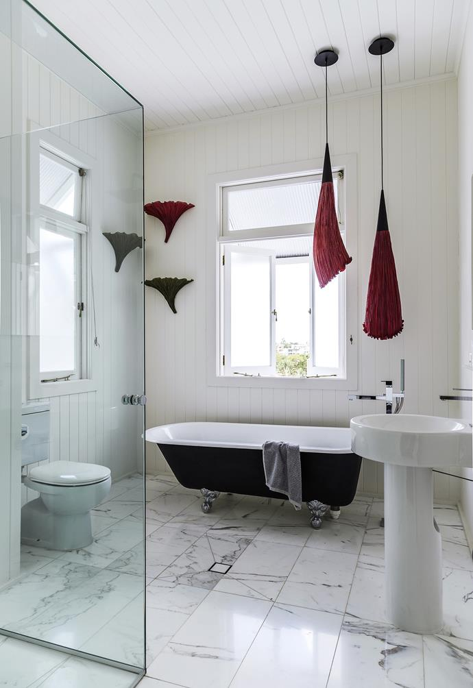"""In the main bathroom the cast-iron bath and vertical joinery are nods to the cottage's heritage, while sculptural lighting looks to its future. **Basin** and **toilet** from [Caroma](http://www.caroma.com.au/?utm_campaign=supplier/