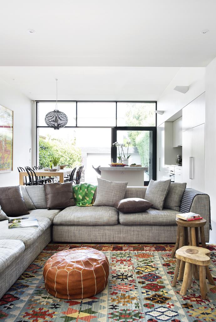 """Global influences abound. The living space, in the main part of the modern box extension at the rear of this old Victorian cottage, is anchored by a kilim purchased in Turkey, a Moroccan ottoman and timber side tables from Amsterdam. **Sofa** from [Arthur G](http://www.arthurg.com.au/?utm_campaign=supplier/