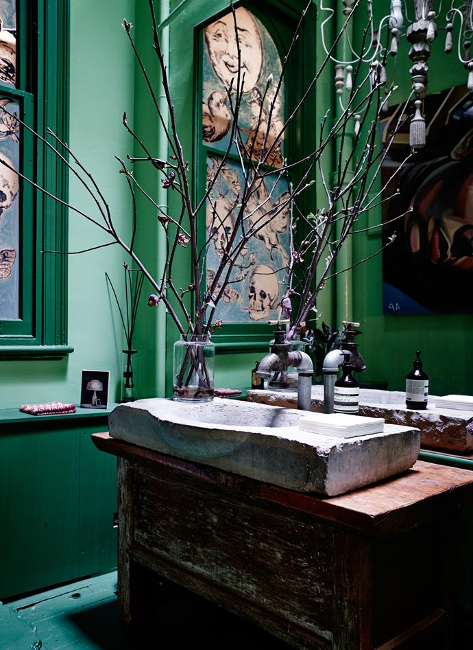 In the style-clashing but fabulous bathroom, a French stone basin sits confidently alongside an industrial brass tap and David Bromley painting.