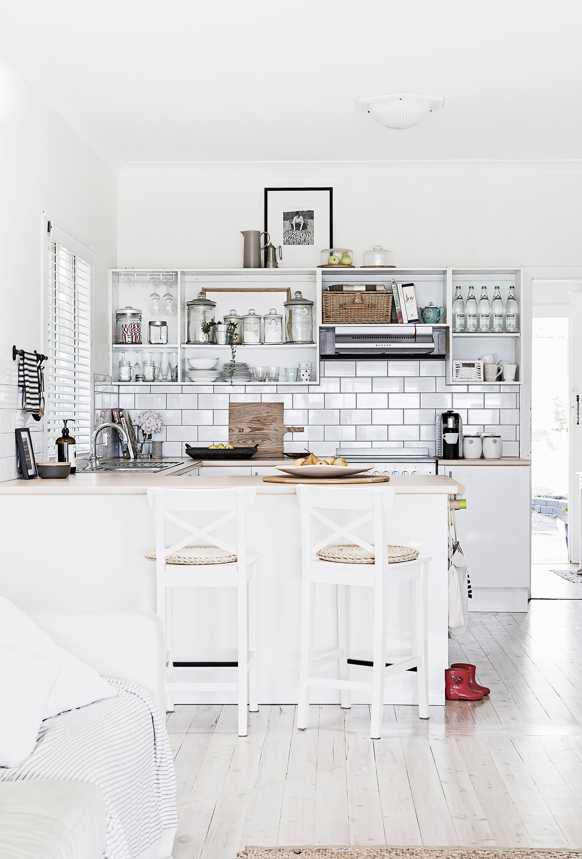 "Simple white subway splashback tiles contrast beautifully with the wooden benchtops in this contemporary kitchen. [See more from this home here](http://www.homestolove.com.au/gallery-stella-and-michaels-coastal-dream-comes-true-2621|target=""_blank""). Photo: Julian Kingma 