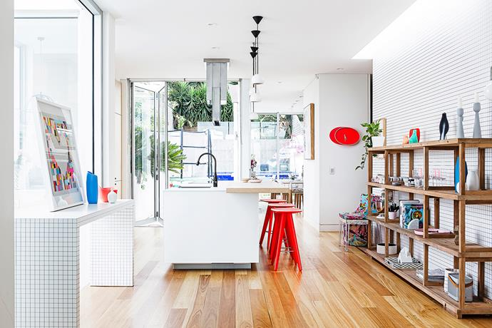 A strategically placed skylight provides natural illumination for the art and homewares on display in the kitchen. A hit of red in the stools and clock lifts the space.