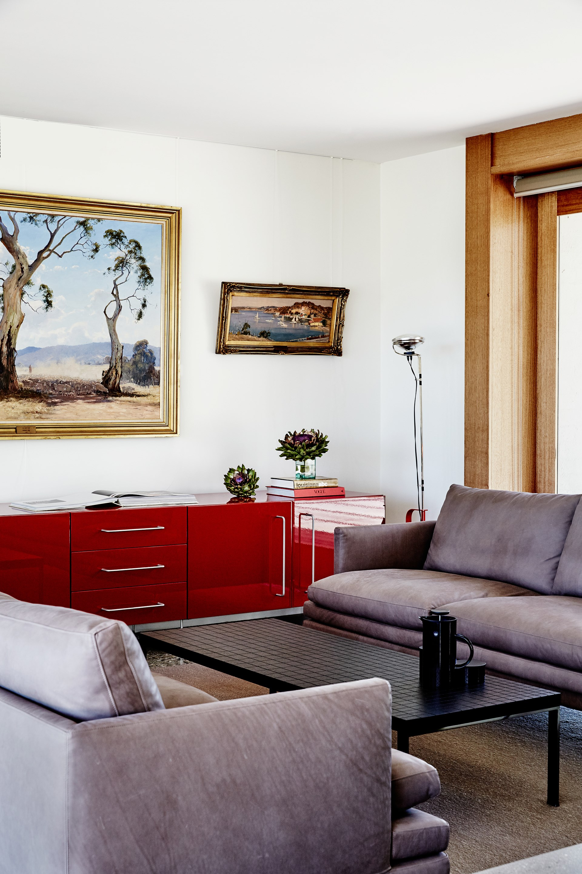 'William' three-seater **sofas** by Zanotta face off across a 'Geometrie' **coffee table** by Poltrona Frau. The red **sideboard** is a Cappellini 'Plan' unit. **Artworks** are by Leonard Long (centre) and Robert Johnson.