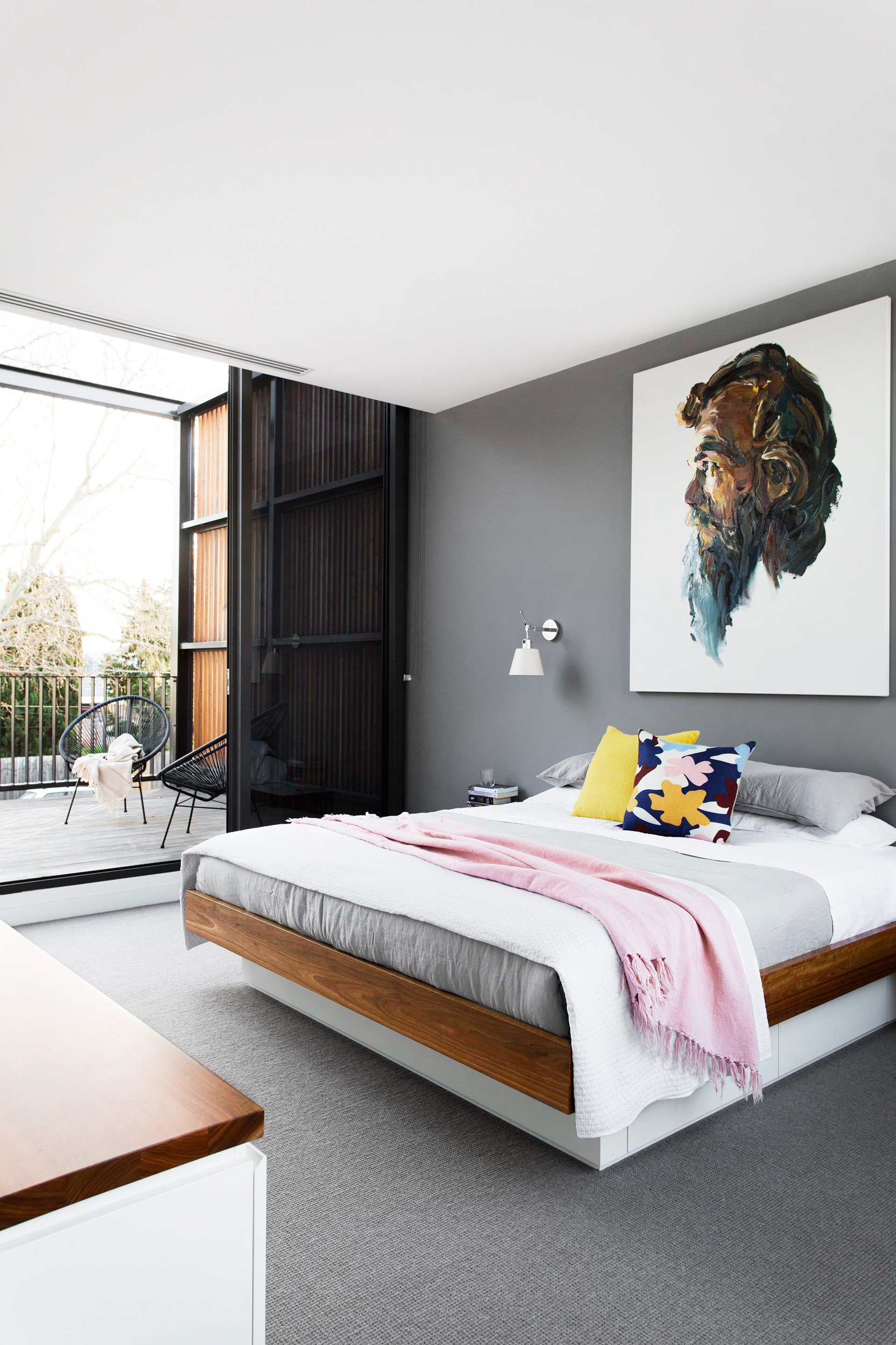 "The feature wall in the main bedroom of [comedian Dave Hugh's home](http://www.homestolove.com.au/gallery-funny-side-up-dave-hughes-2659|target=""_blank"") is painted in Dulux Timeless Grey. Soft greys emerge in the layers of linen from Linen & Moore, topped with bright cushions from Safari Living. The portrait is the work of another well-known comedian, Anh Do. Photo: Martina Gemmola / *Australian House & Garden*"
