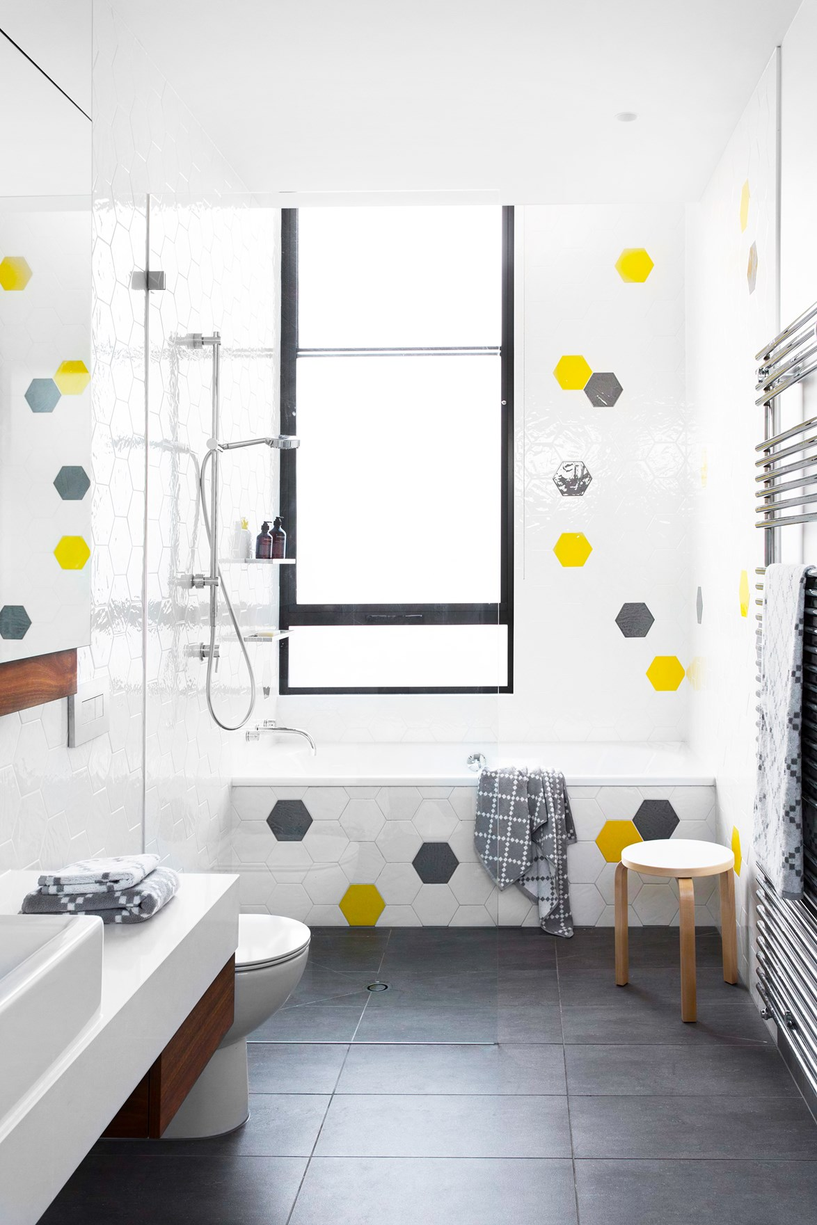 "When it came to building a home that would grow with his family, [comedian Dave Hughes](https://www.homestolove.com.au/gallery-funny-side-up-dave-hughes-2659|target=""_blank"") chose a bathroom that maximises light and space. Statement hexagonal tiles are the hero-piece, while the built-in tub takes a backseat. *Photo: Martina Gemmola / Styling: Toni Briggs / Story: Australian House & Garden*"