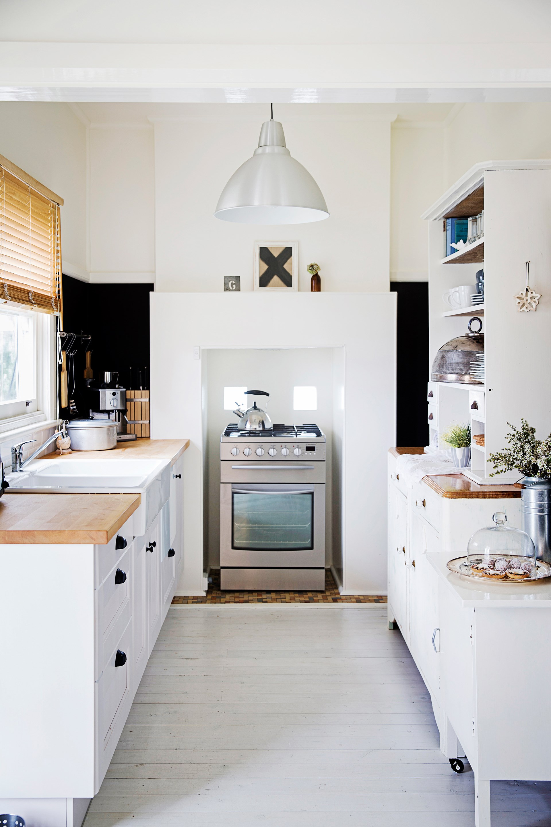 """Homeowners Beth and Warren turned an old weatherboard boatshed in the sleepy village of Erowal Bay, NSW, into a stylish waterfront home using upcycled wares, heirlooms and elbow grease. In the kitchen, whitewashing the floor and injecting plenty of white and timber added a beachy feel. """"I love the drama of the black walls against the white Ikea cabinets,"""" Beth says. [Take the tour](http://www.homestolove.com.au/gallery-beth-and-warrens-idyllic-beach-house-renovation-2529/?utm_campaign=supplier/