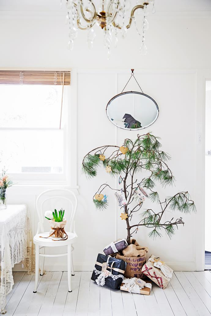 Work with your existing style when decorating for Christmas. A single tree branch looks effective against the bright, white walls and floors.