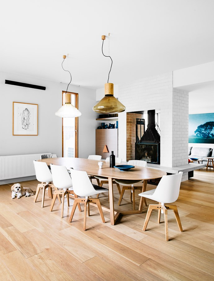 """Comfort can come in the form of a beautiful fireplace, as interior designer Fiona Lynch shows in the Melbourne dining area. """"It's the starring feature of this room,"""" she says. High ceilings allow for the inclusion of generous Brokis Muffin **pendant lights**, an eight-seat Lowe Furniture Atticus **table** and MDF Italia Flow **dining chairs**, all from [Hub Furniture Lighting Living](http://www.hubfurniture.com.au//?utm_campaign=supplier/