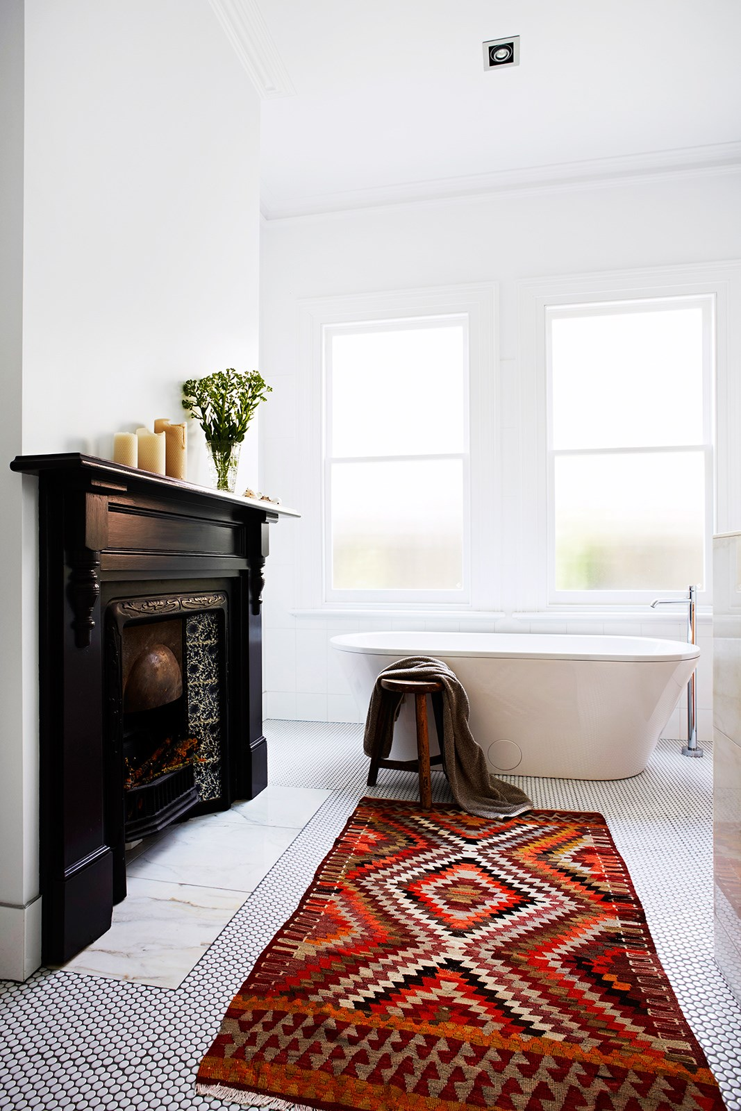 """A fireplace is a great talking point in this light-filled bathroom within a [century-old home](http://www.homestolove.com.au/gallery-paula-and-martins-dramatic-timber-home-renovation-2015-1413