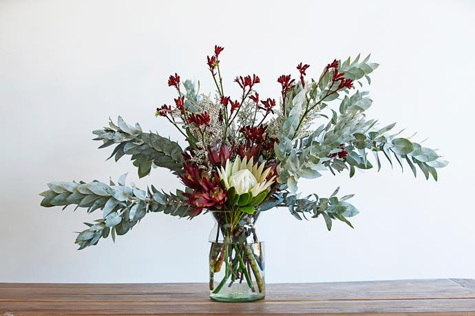 The theme for my arrangement is quite simple: natives. The different components include Eucalyptus macrocarpa, Leucadendron 'Safari Sunset', Protea 'King White', kangaroo paw and thryptomene. They all have different interesting textures and colours that complement each other. Also, as it's summer, I wanted to create something that doesn't need heaps of care or attention. Plus, I think the shapes give a bit of a festive vibe. They're not really seasonal, which is great. They have certain months when they are available in abundance, but they're around for the majority of the year. I try to stay away from anything too as I think arrangements can sometimes look contrived and I prefer them to be natural. I like when the focus is on the shapes and natural forms of the plants and flowers, not the manipulation of them. That's why I chose a thick glass vase with a flared mouth – it allows the arrangement to sprawl out and not be so constricted.