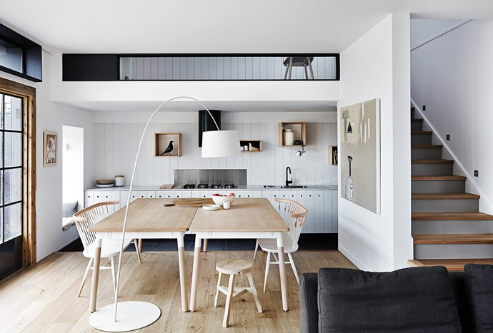 The central, open kitchen houses an oversized table that becomes a bench-height space when you step down to the kitchen level. The glazed section above the kitchen provides a visual link to a mezzanine level, allowing light in and creating a sense of connectivity.