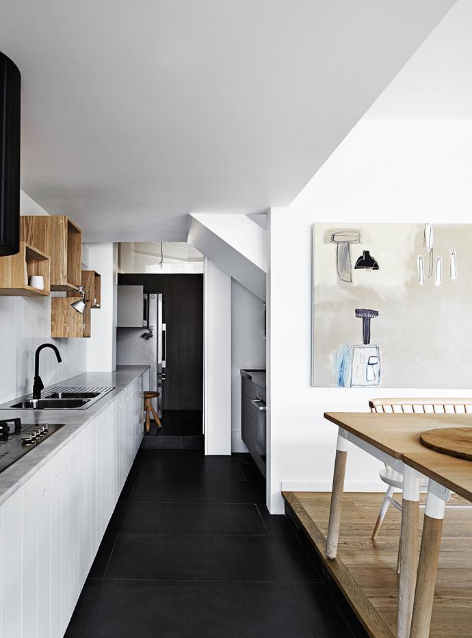 In the kitchen, the walls and cabinet doors are clad in pine boards painted white. The doors feature fingerpulls instead of handles for a clean finish.
