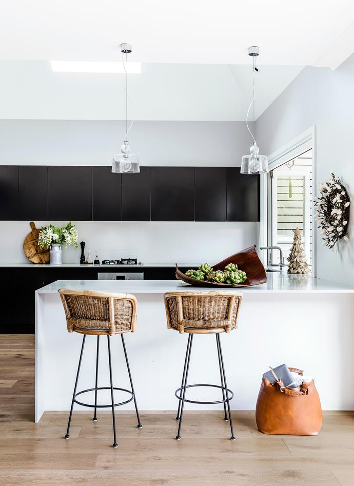 Black cabinets bring a modern touch, but the otherwise bright, white kitchen maintains a relaxed vibe.