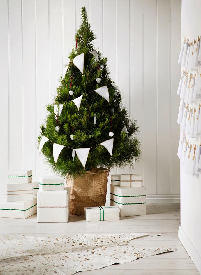 "Tree decorations needn't be complicated. This simple white cotton bunting glows against a lush green pine. Radiata **pine tree** from [Dural Christmas Tree Farm](http://www.duralchristmastreefarm.com.au/?utm_campaign=supplier/|target=""_blank""), in Robert Gordon **copper basket** from [Chef and The Cook](http://www.chefandthecook.com.au/?utm_campaign=supplier/
