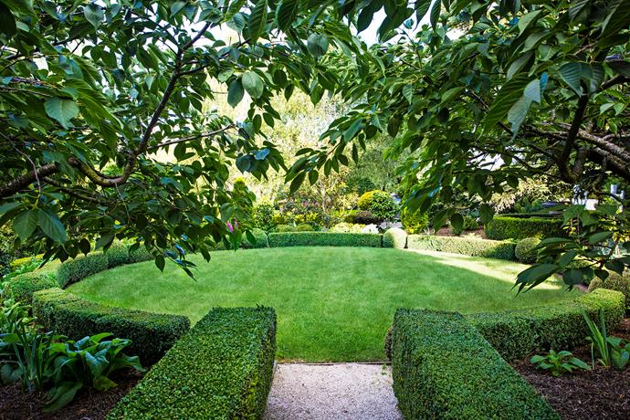 The circular lawn near the home's front entrance features the transplanted hedging.