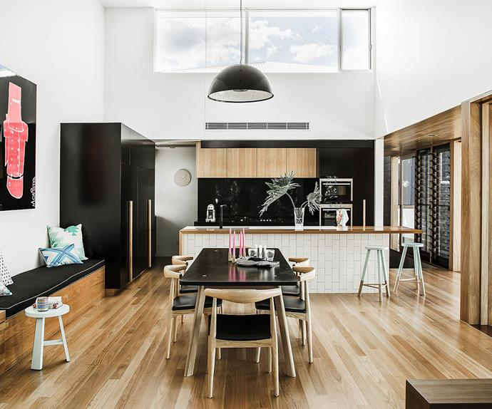 Open plan black and timber kitchen and dining room