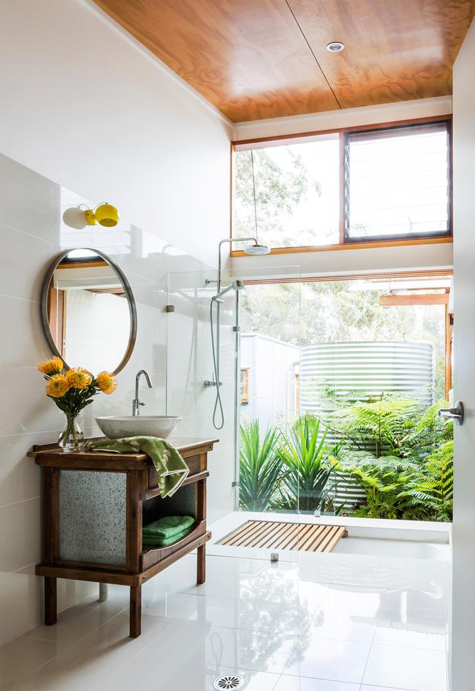 """Sleek and earthy textures work in harmony in the bathroom. Ceiling, marine ply. **Tiles**, [Rivoland](http://www.rivoland.com.au//?utm_campaign=supplier/ target=""""_blank""""). **Bath**, [Caroma](http://www.caroma.com.au//?utm_campaign=supplier/ target=""""_blank""""). Custom-made vanity in reclaimed hardwood. Handmade basin by pottery artist John Payne. **Mirror**, [Ikea](http://www.ikea.com/au/en/preindex.htm/?utm_campaign=supplier/ target=""""_blank""""). Wall light from [BoConcept](http://www.boconcept.com/en-au//?utm_campaign=supplier/ target=""""_blank"""") in Germany."""