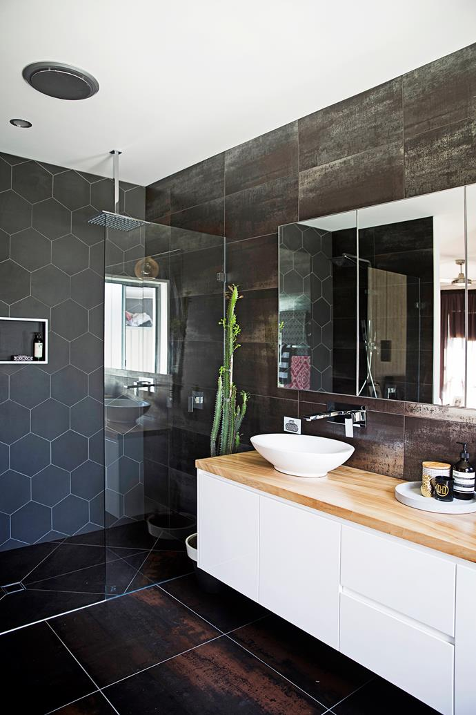 In the bathroom, Julie and Jeremy have created a moody ambience with charcoal hexagonal tiles.