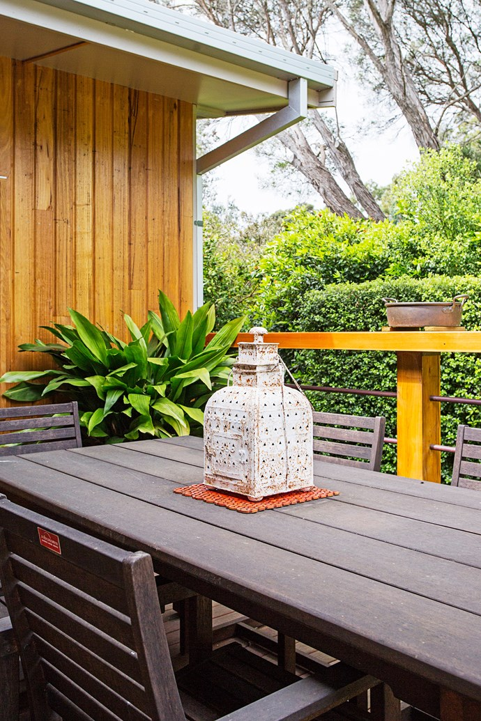 An old hurricane lantern adds charm to the outdoor dining setting.