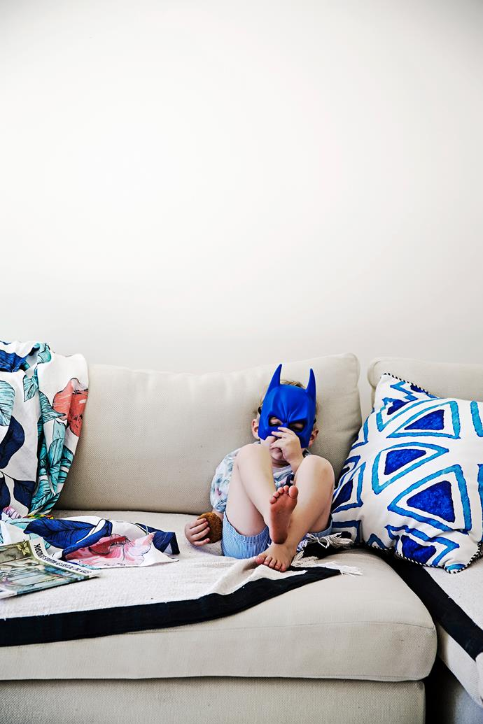 Kelli's son Hunter, nestled among cushions from Talulah's homewares range, enjoys playtime in a family room that was converted from a bedroom.