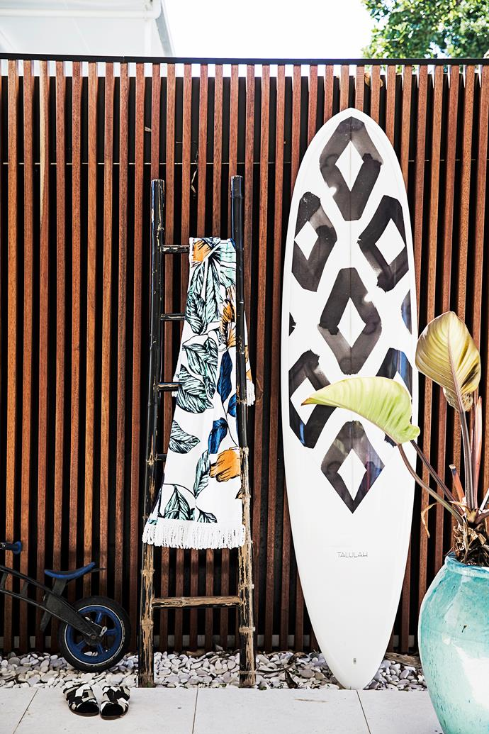 A garage built from merbau timber, seen opposite, is at the front of the property. This is where the family's surfboards live, including this mini mal from Kelli's label Talulah.