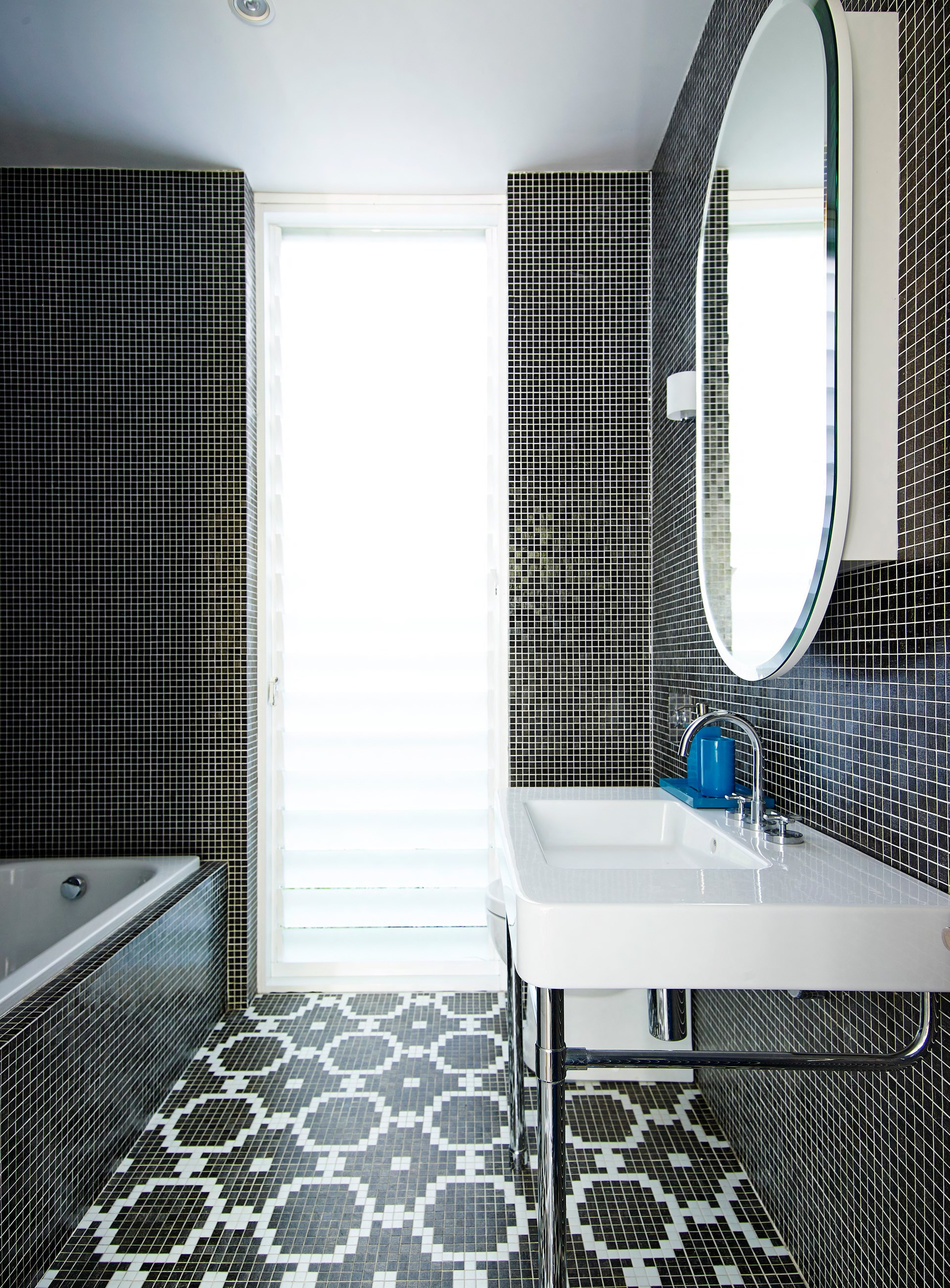 "Black and white mosaic tiles create a monochrome masterpiece in the main bathroom of this [renovated worker's cottage](http://www.homestolove.com.au/from-workers-cottage-to-fabulous-family-home-2502|target=""_blank""). Photo: Anson Smart / *Australian House & Garden*"