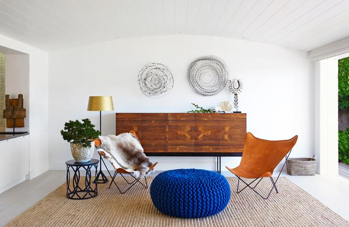 """In the living room, wire sculptures from Tracey Deep Floral Sculptures make a statement above a sideboard that the owner bought in London. Leather **chairs** from [Pure and General](http://www.pureandgeneral.com/ target=""""_blank""""). **Reindeer skin** from [Les Interieurs](http://www.lesinterieurs.com.au/ target=""""_blank""""). Knitted blue **ottoman** by [Thomas Eyck](http://www.thomaseyck.com/ target=""""_blank""""). Tom Dixon **lamp** from [Dedece](http://www.dedece.com.au/ target=""""_blank""""). **Side table** from [Arida](http://www.arida.com.au/ target=""""_blank""""). **Pot** from [Garden Life](http://www.gardenlife.com.au/ target=""""_blank""""). **Jute rug** from [International Floorcoverings](http://www.interfloors.com.au/ target=""""_blank"""")."""