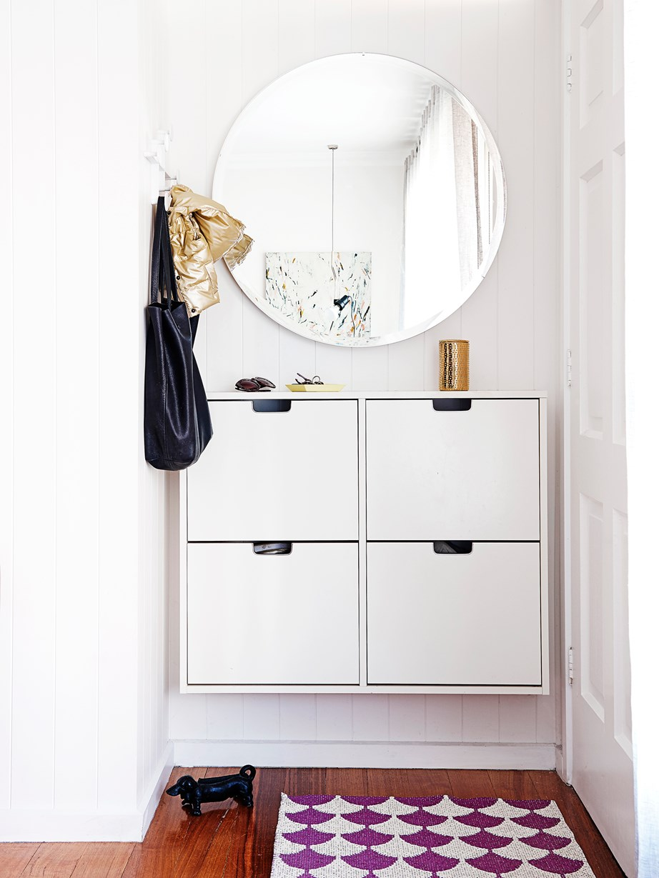 "Interior designer Lauren Li created an ""entry"" in this compact space with a wall-mounted shoe storage cabinet from IKEA, a beautiful round mirror, hooks and rug."