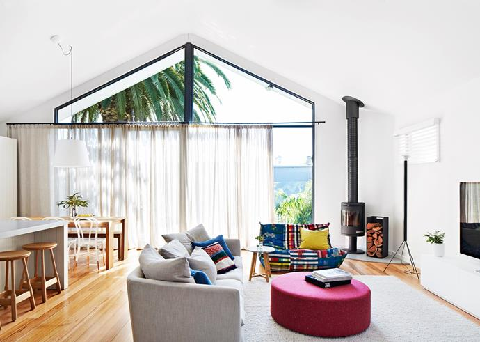 """My favourite spot in the house is the settee near the fireplace, where I sit and read to Roko,"" says Tonci. Fireplace and wood box, Wignells of Melbourne. Cleo (grey) **sofa** and Iko **side table**, [Jardan](http://www.jardan.com.au//?utm_campaign=supplier/