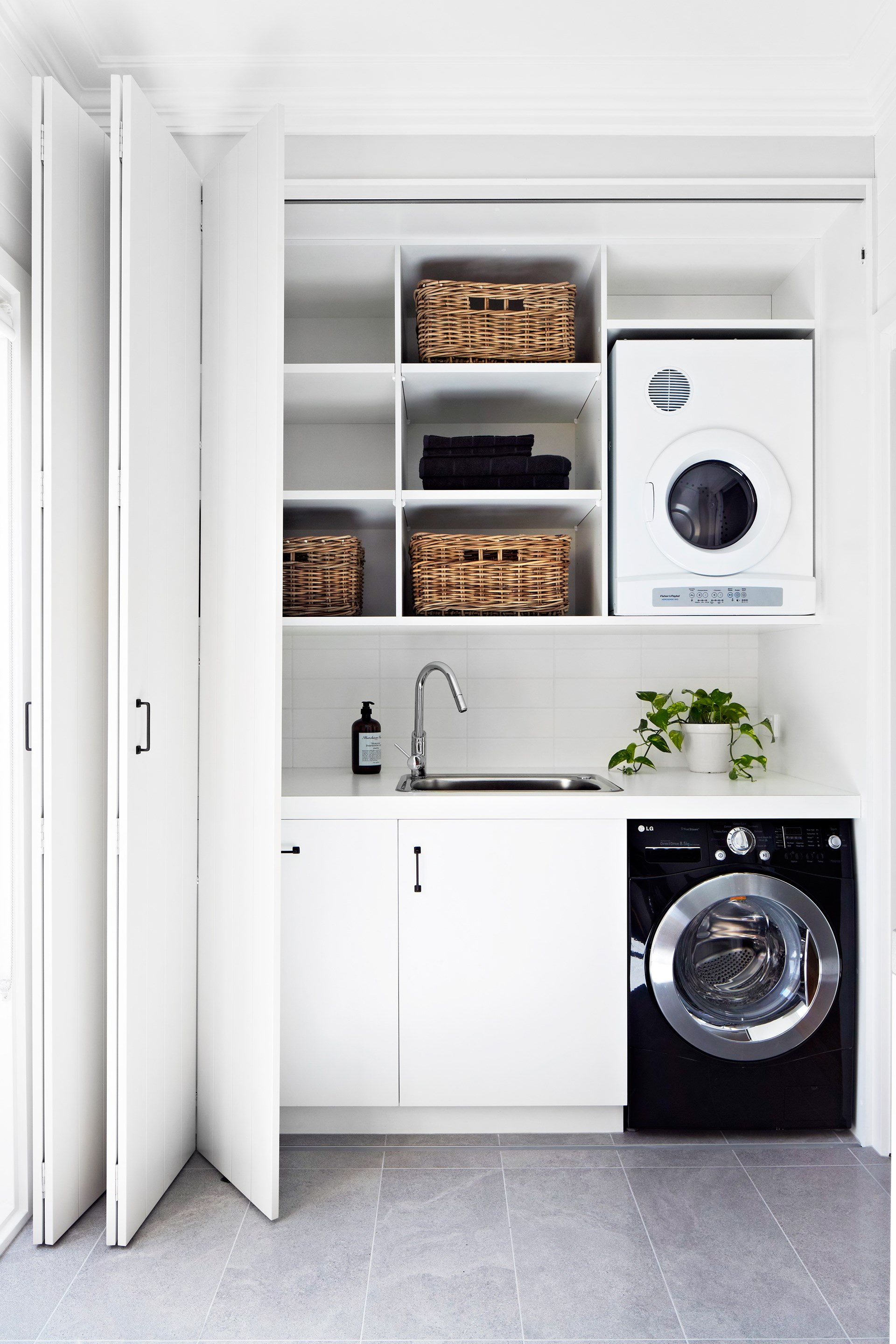 "Keeping a [small laundry](https://www.homestolove.com.au/how-to-design-a-small-space-laundry-5269|target=""_blank"") like this is order means utilising any spare surface area for storage with built-in shelves, baskets and hooks. *Photo:* Armelle Habib / *Australian House & Garden*"
