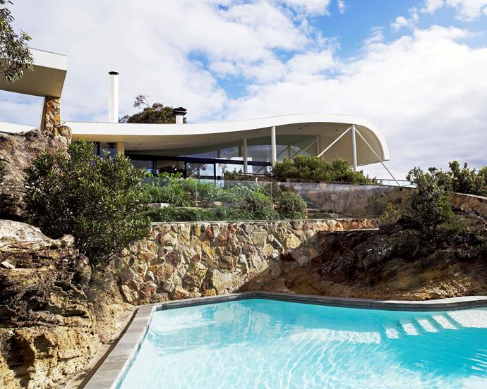 The swimming pool is naturally shaped by the two rock cliffs that surround it, and offers ample water supply in case of bushfires. A frameless glass balustrade slots into the rock face. The curved line of the roof with its rise and dip gives the house its sinuous form.