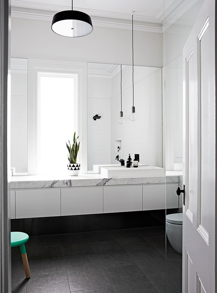 """We wanted the window as the centrepiece in the bathroom, so we created a long marble bench with sinks either side,"" Johanna says. The door adds a traditional touch to the modern space."