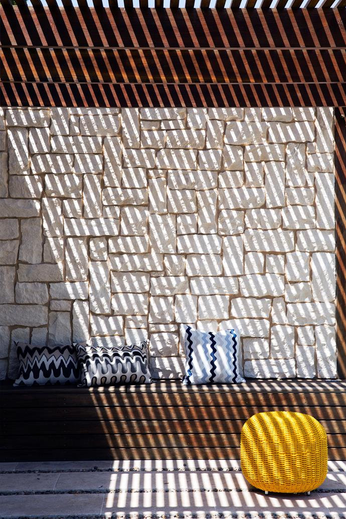 "The slatted roof over the front pergola sends slender shadow lines onto the seating area, creating a wonderful graphic pattern. The stone wall is made from limestone cladding, Newport Random Ashlar from [Eco Outdoor](https://www.ecooutdoor.com.au/|target=""_blank""). The timber is tallowwood, an Australian hardwood that will turn silvery-grey over time. Matt has installed uplights to send shafts of light up the rock face at night."