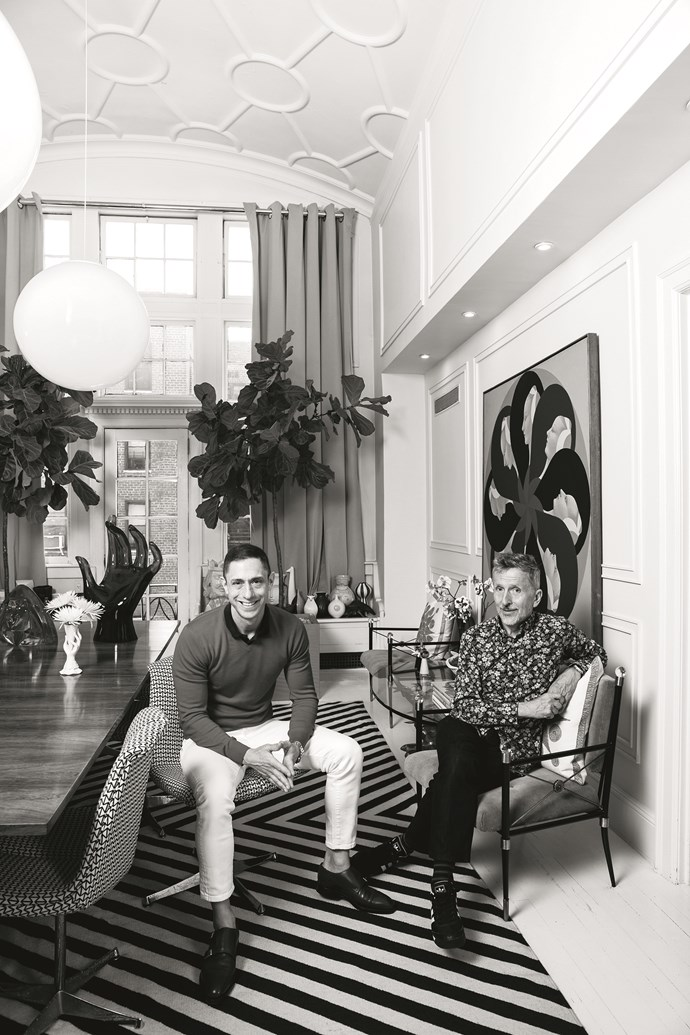 Jonathan Adler and Simon Doonan in the dining room beside a Santi Graziani artwork.