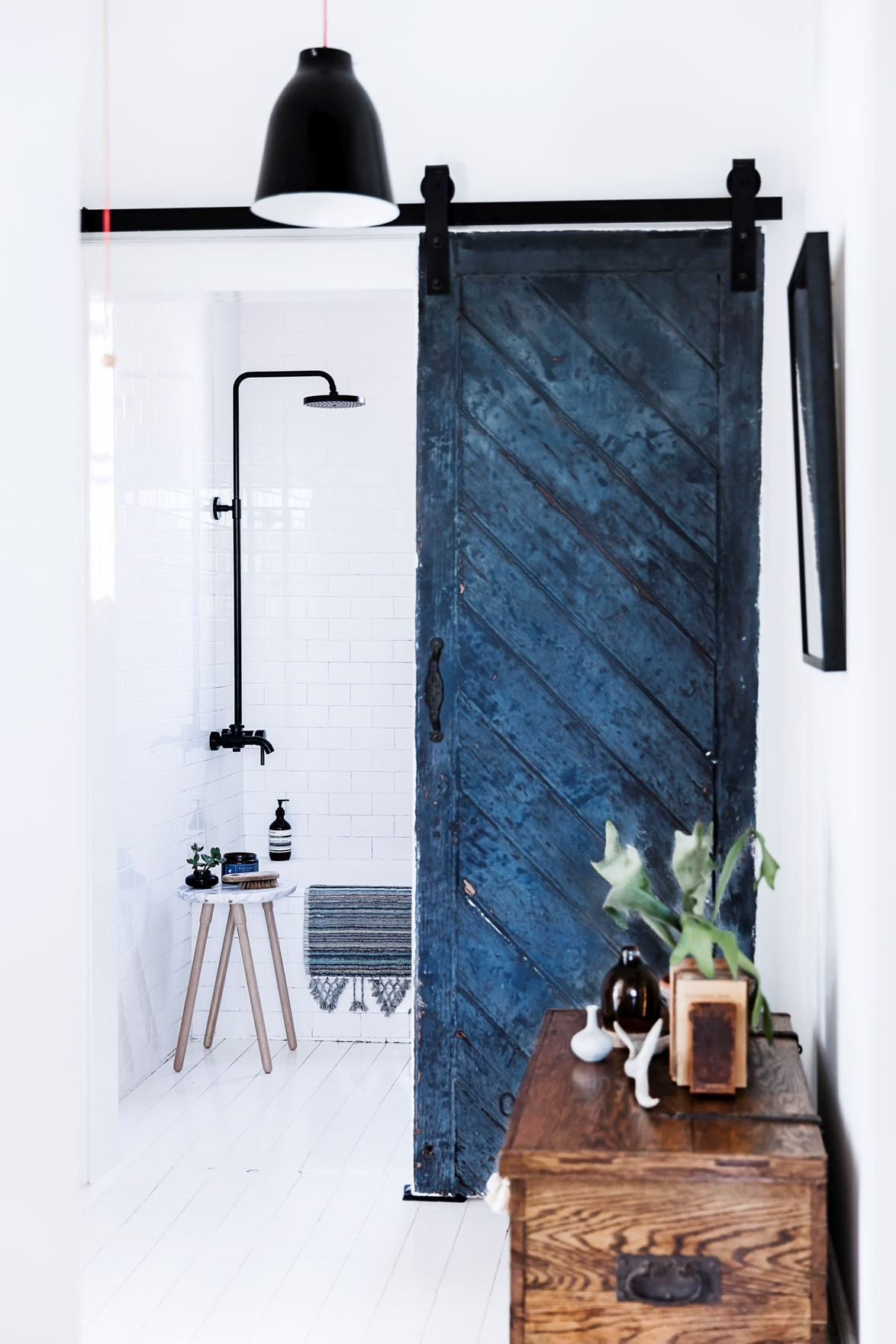 "Subway tiles and timber flooring are both staples of country style bathrooms. In this [Scandi style Sydney apartment](https://www.homestolove.com.au/sydney-apartment-gets-swedish-summer-house-makeover-3050|target=""_blank""), the farmhouse look has been given a contemporary twist with matte black tapware and a sliding barn door in a striking shade of indigo. *Photo: Maree Homer / Styling: Kerrie-Ann Jones / Story: Real Living*"