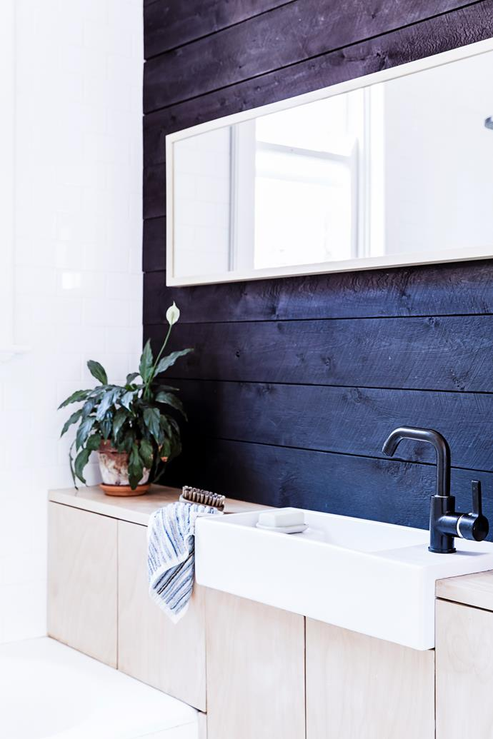 "Fräg was advised not to use the colour black in the small bathroom, but he wanted a simple colour palette in his home. The timber wall is painted in Feast Watson ""Prooftint"" in Black, finished with a matte varnish."