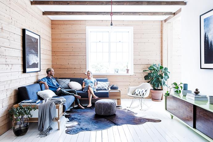 "A key living room feature is the pine wall, laid horizontally. ""A horizontal line is more calming and peaceful whereas a vertical application creates height and more drama,"" says Fräg, pictured with his wife Naomi on a sofa he designed. He chose untreated pine because it's ""light, blonde, utilitarian, humble"". Rug from [Great Dane Furniture](http://www.greatdanefurniture.com/