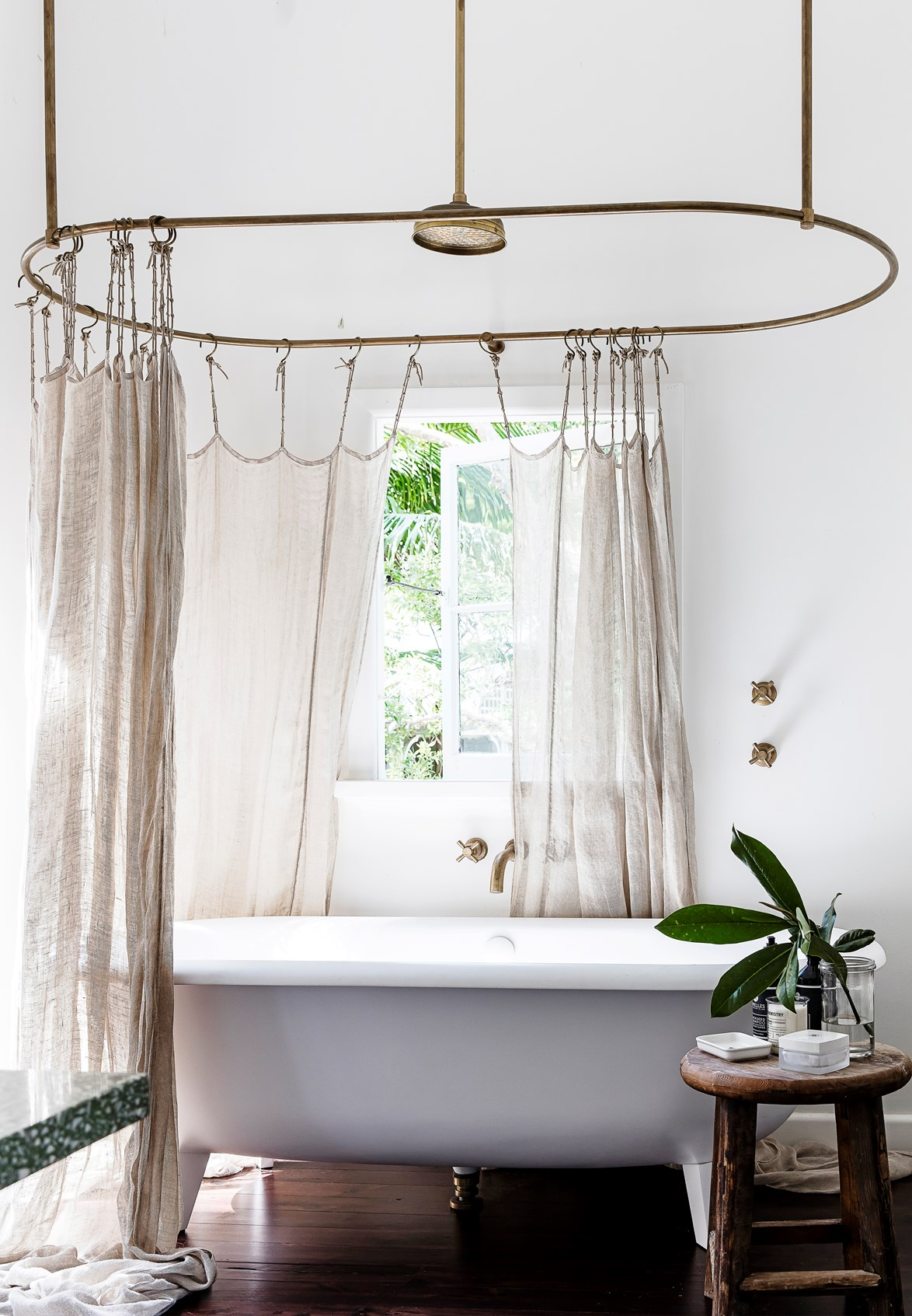 "Former *Real Living* editor [Deb Bibby's beach shack](https://www.homestolove.com.au/pittwater-beach-shack-gets-a-heartfelt-renovation-3064|target=""_blank"") bathroom is a lesson in modern Australian country style. Brass detailing and linen-look shower curtains are the perfect combination of relaxed and refined. *Photo:  Maree Homer / Story: Real Living*"