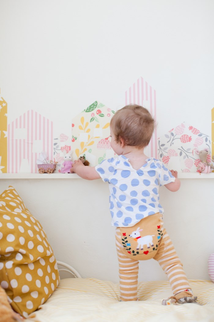 """Cut out some house shapes in various patterns for a cute wall decal in a children's bedroom. Get the DIY [here](http://www.thislittlestreet.com/blog/2015/06/01/diy-row-of-wallpaper-houses/?utm_campaign=supplier/