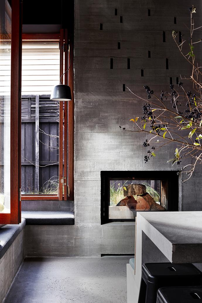 The fireplace and chimney are a focal point of the kitchen, rising past the double-height void that spans half the space.