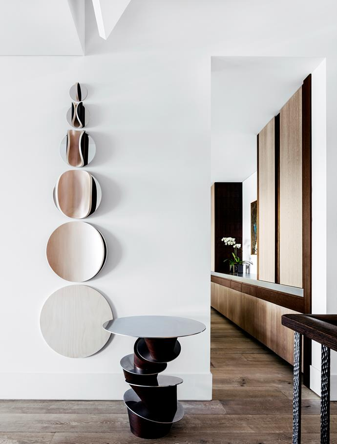 """In the entry hall and dining room, 'Rachis' table in polished nickel with chocolate greyed oak by [Hamel + Farrell](http://hamelandfarrell.com/collection/hf1-0/