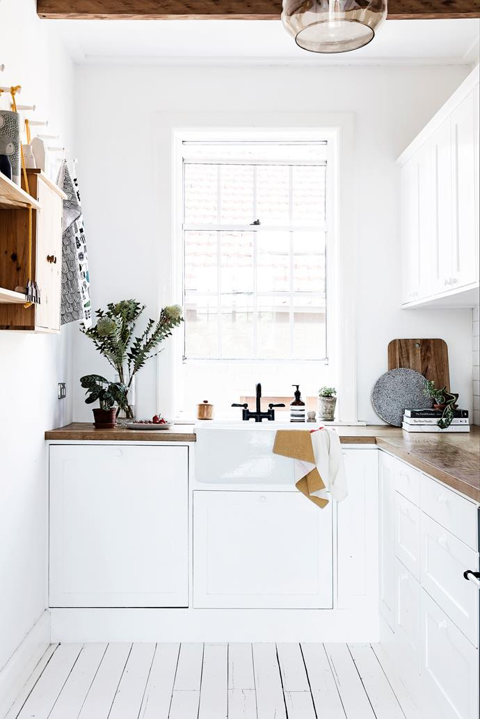 "Fräg used the original kitchen cupboard framework to create a new design. The timber beams are purely aesthetic, adding warmth to the white space. [Take a full tour of the home here]((http://www.homestolove.com.au/sydney-apartment-gets-swedish-summer-house-makeover-3050/?utm_campaign=supplier/|target=""_blank""). Photo: Maree Homer / *real living*"