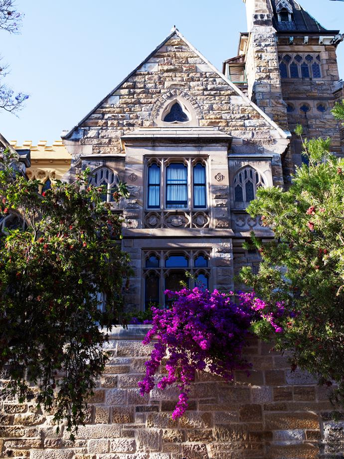 The impressive sandstone facade of The Abbey in Annandale, Sydney, framed by a lush garden designed by William Dangar.