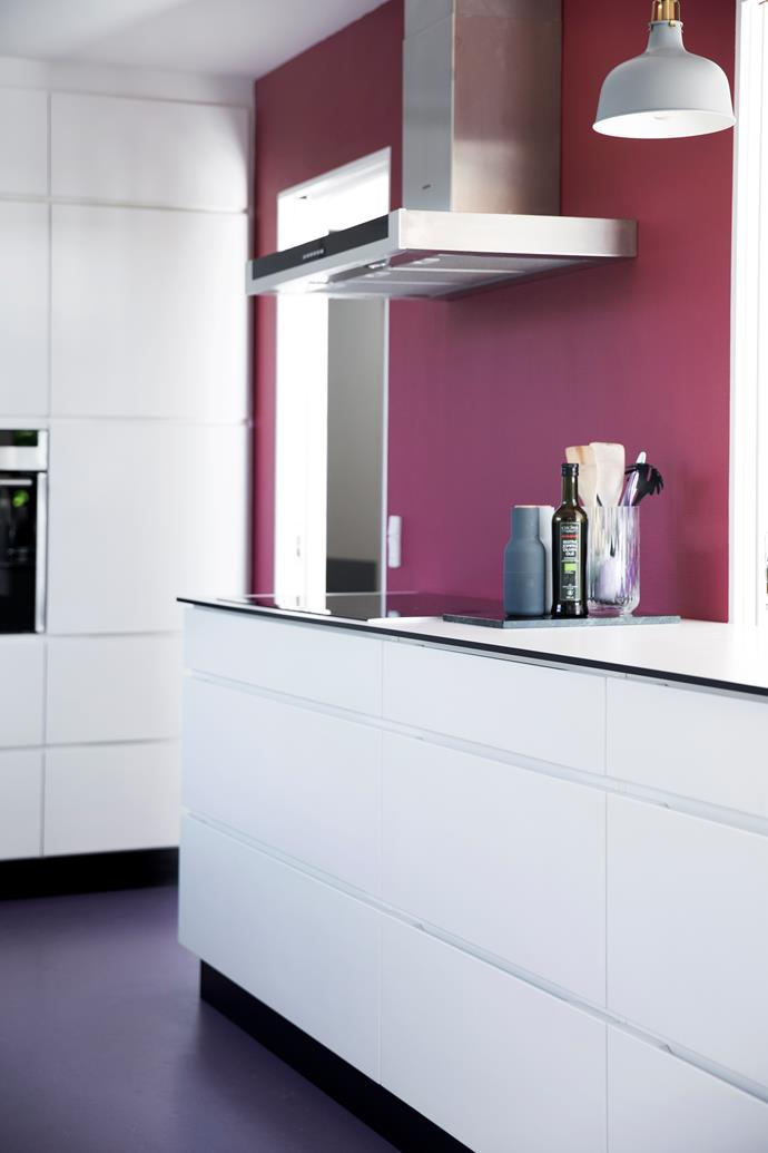 A raspberry red wall in the kitchen complements the purple linoleum floor.
