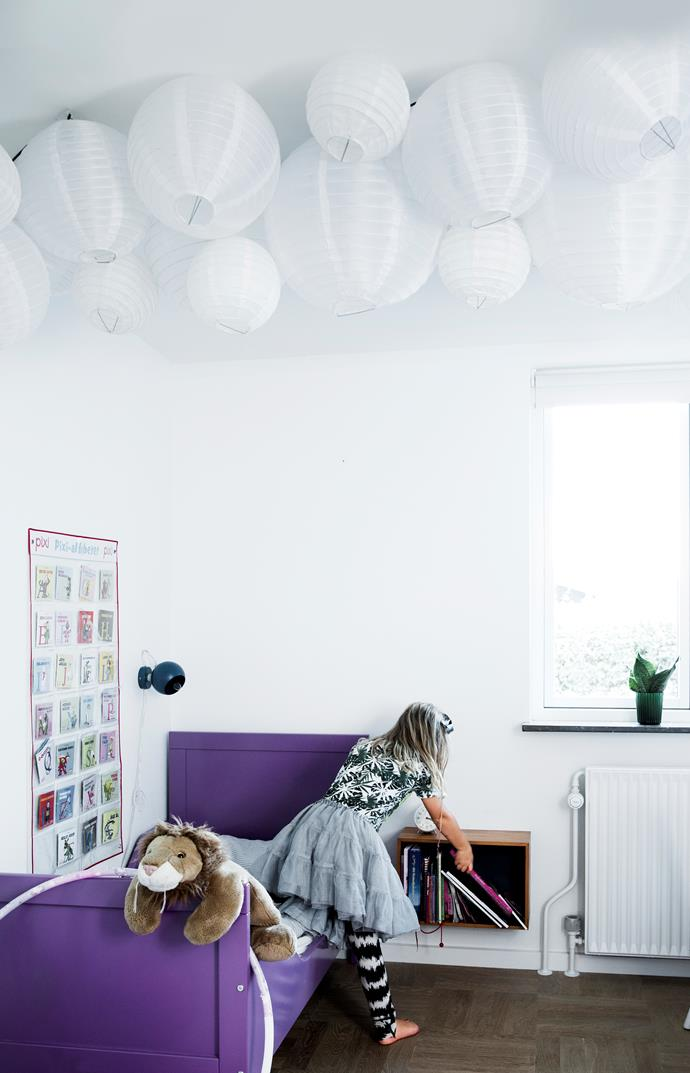 Lærke's bed is a vivid purple, similar to the lino floor in the kitchen. A single string of bulbs, festooned with paper lamps,  ensures a cosy atmosphere in the evenings and its sculptural form looks beautiful by day.