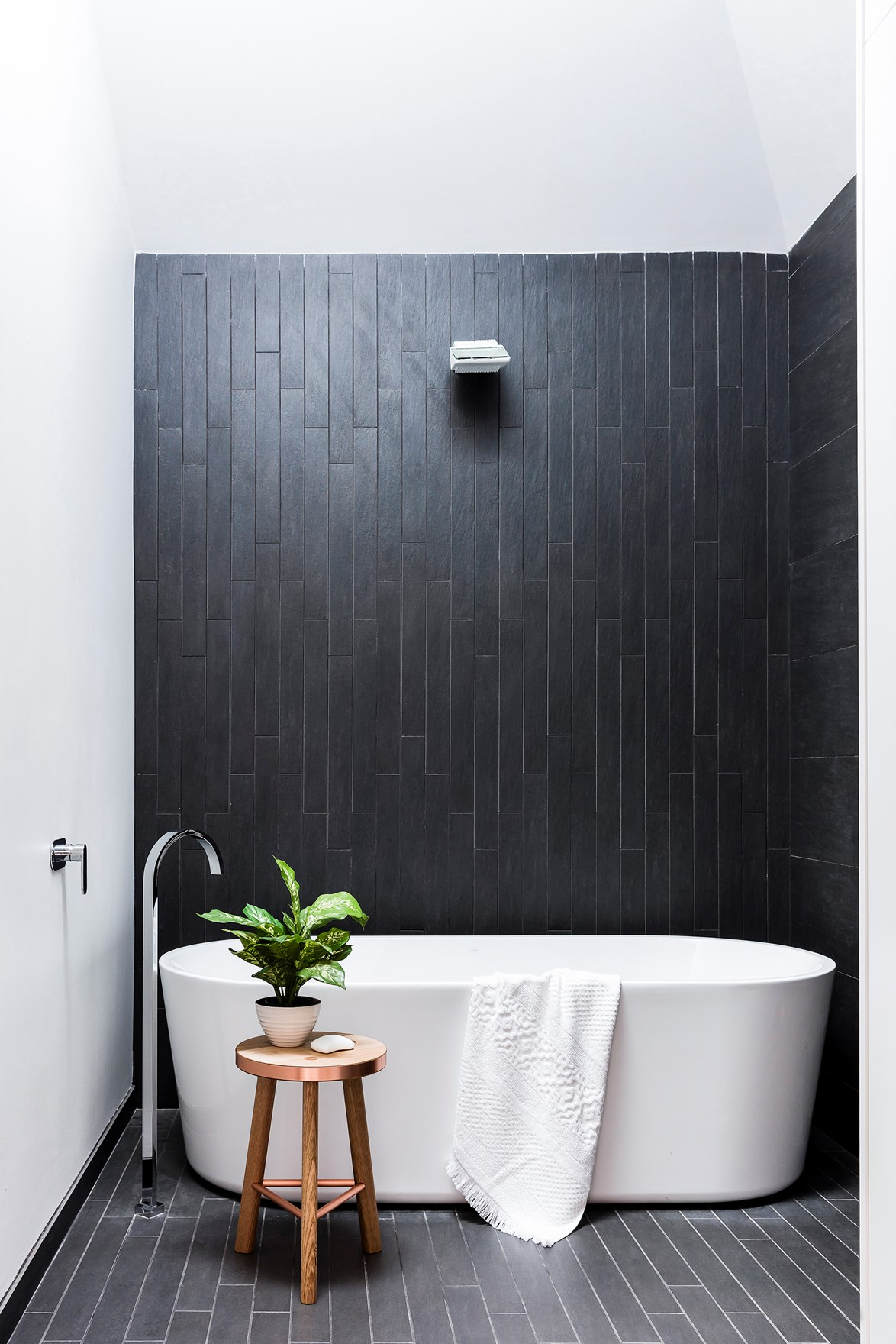 """A lightwell illuminates the moody, charcoal ceramic tiles in this [black and white bathroom](https://www.homestolove.com.au/10-timeless-black-and-white-bathrooms-4583